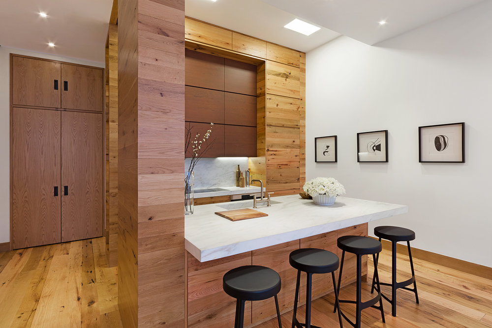 Kitchen with abundant wood accents throughout the space and abstract art on the wall. MEP provided by 2L Engineering.