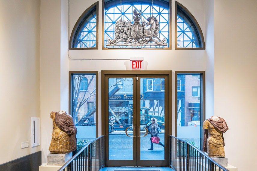 The entrance of Lapicida with Roman busts on either side of the window doors looking out to a woman walking on the New York sidewalk. MEP provided by 2LS Consulting Engineering.