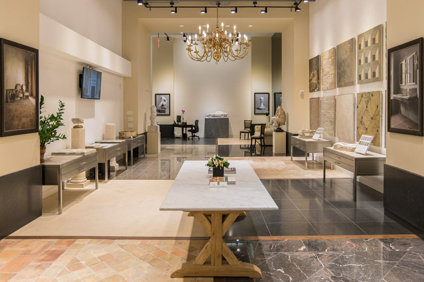 A table in the center of Lapicida's showroom in New York, with a variety of natural stone samples decorating the walls and lining the floors for display. MEP designed by 2L Engineering.