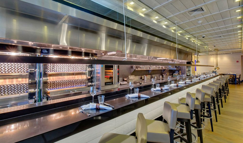Bar area facing a food preparation station with napkins, plates, and cutlery organized on the counter and light beige seats. MEP provided by 2L Engineering, a New York based firm.