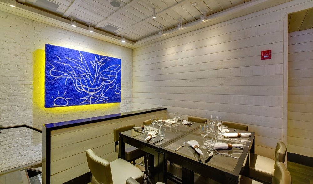 Dining area facing a large blue painting of an abstract, cubist, chicken with yellow back lighting in Le Coq Rico, a bistro and bar in New York. MEP designed by 2LS.