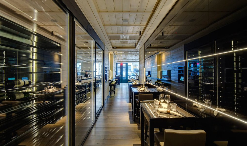 Seating areas with wine fridges on either side of the wall in Le Coq Rico, an attractive bistro and bar owned by renowned French chef. MEP designed by 2L Engineering.
