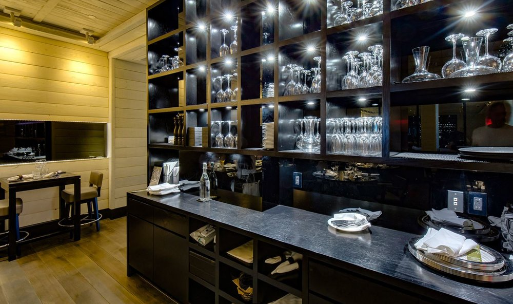 Server area with wine glasses and carafes on a wooden shelving unit in Le Coq Rico, a bistro bar restaurant specializing in sophisticated poultry dishes. MEP by 2LS Consulting.