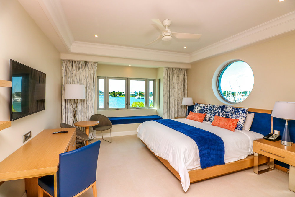 Harbor Club Hotel guest bedroom with blue accents and wood furniture overlooking the harbor at St. Lucia. MEP designed by 2L Engineering.