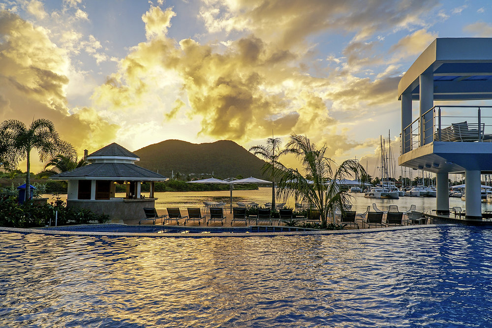 Beautiful sunset behind hills as seen from the pool at the Harbor Club Hotel in St. Lucia. MEP designed by 2L Engineering.