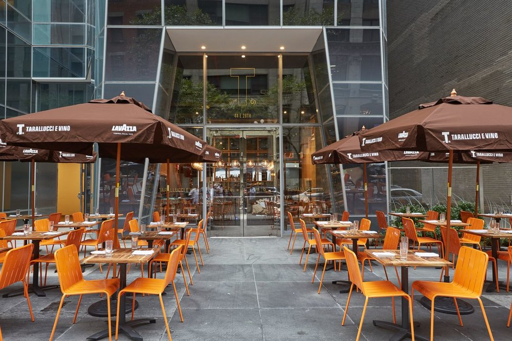 Orange outdoor seating with brown umbrellas at Tarallucci e Vino on 44 East 28th Street, New York. MEP designed by 2LS Consulting Engineering.