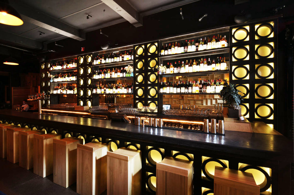 Bar with back lighting on wine bottles and circular designs on the surface in Pearl and Ash, a restaurant and wine bar with MEP by 2L Engineering.