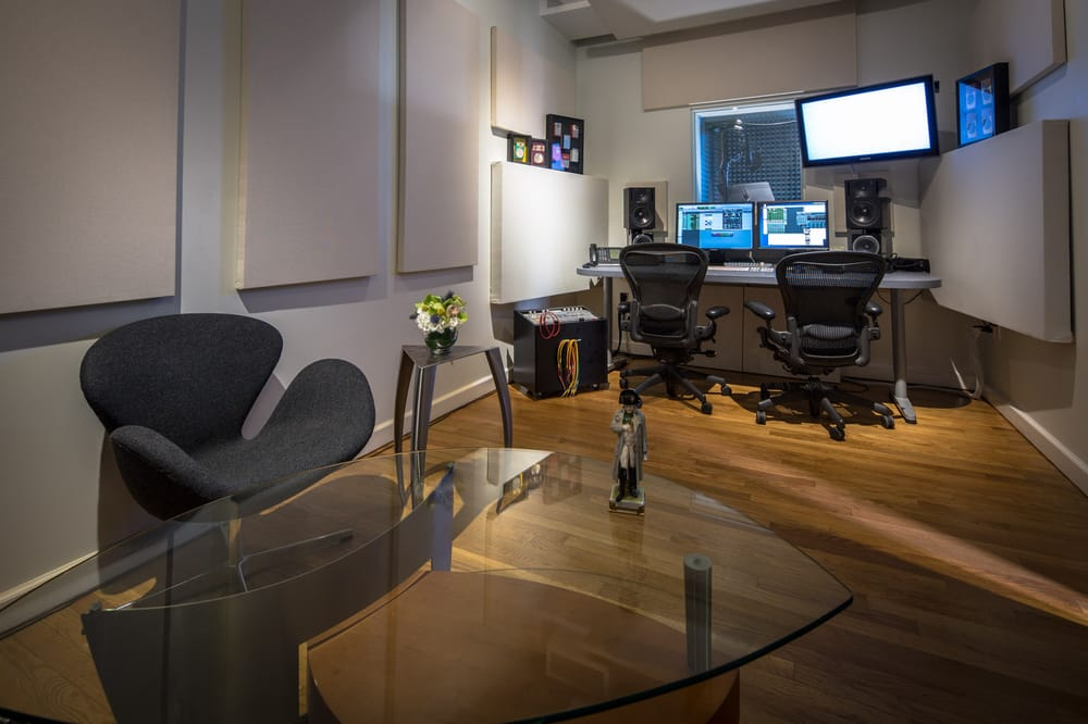 A glass table with a small Napoleon figurine in a recording studio with a sound booth in Napoleon, Brooklyn. MEP designed by 2L Engineering, a New York firm.