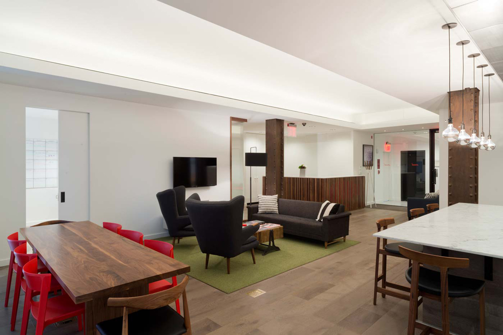 Lounge area and an island table with contemporary design in the kitchen space at the offices of Arcade Edit. MEP provided by 2L Engineering, New York.