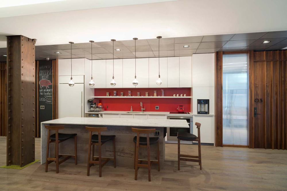 Island at the kitchenette with red accents and a chalkboard in the offices of Arcade Edit in New York. MEP designed by 2L Engineering.