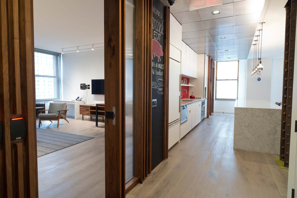 Doors between a brightly lit kitchenette with red accents and a lounge space in the offices of Arcade Edit in New York. MEP designed by 2LS Consulting Engineering.