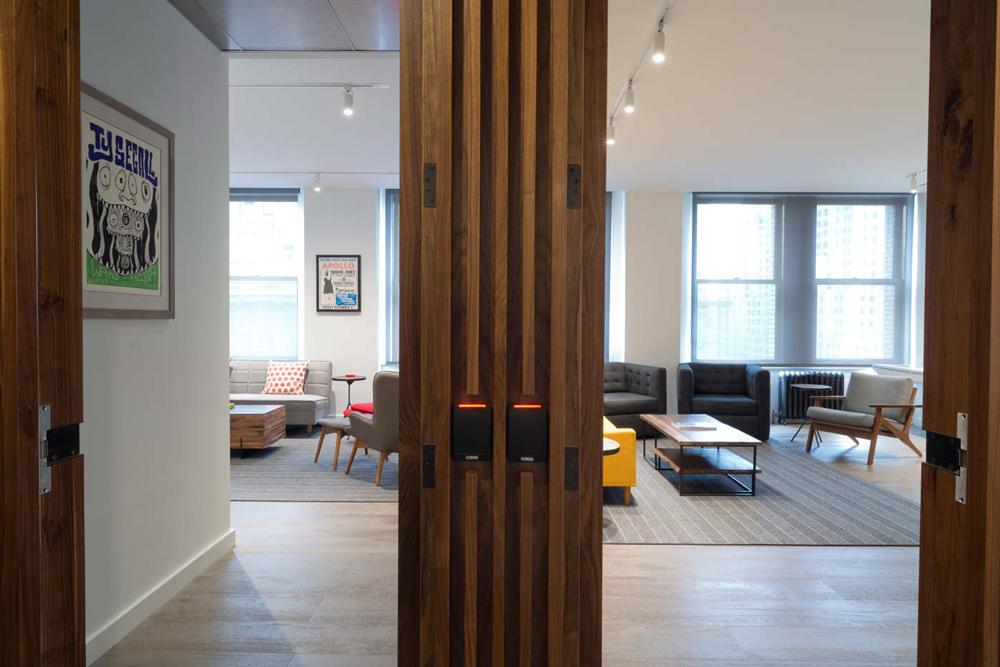 Two wood accented doors leading to separate private lounge areas in the offices of Arcade Edit in New York. MEP provided by 2LS Consulting Engineering.