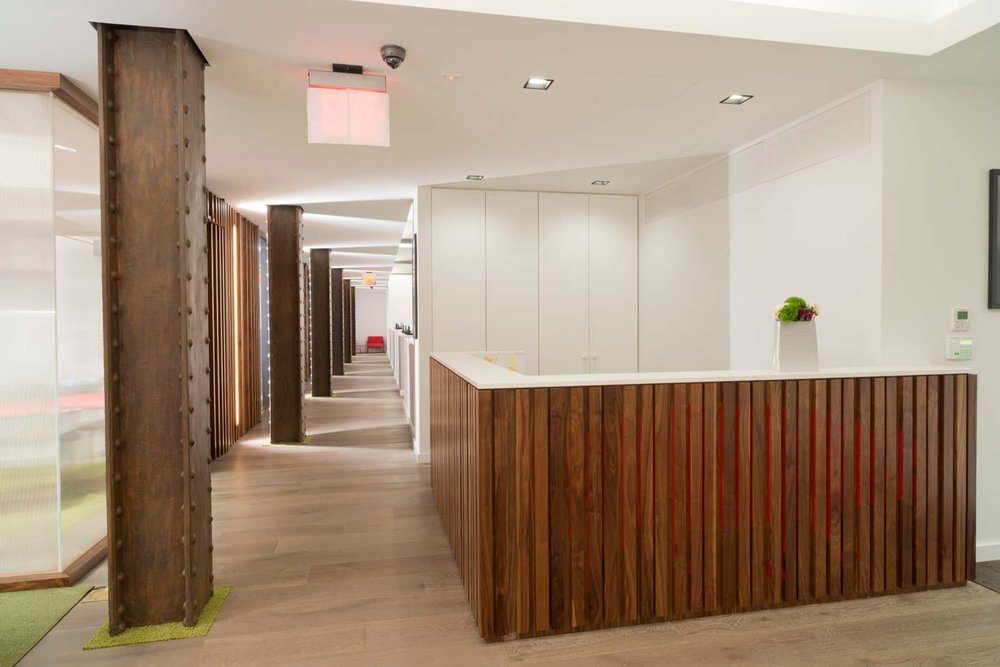 Receptionist area with a wood accent desk and steel, rusted columns leading along the hallway at the offices of Arcade Edit in New York. MEP provided by 2LS.