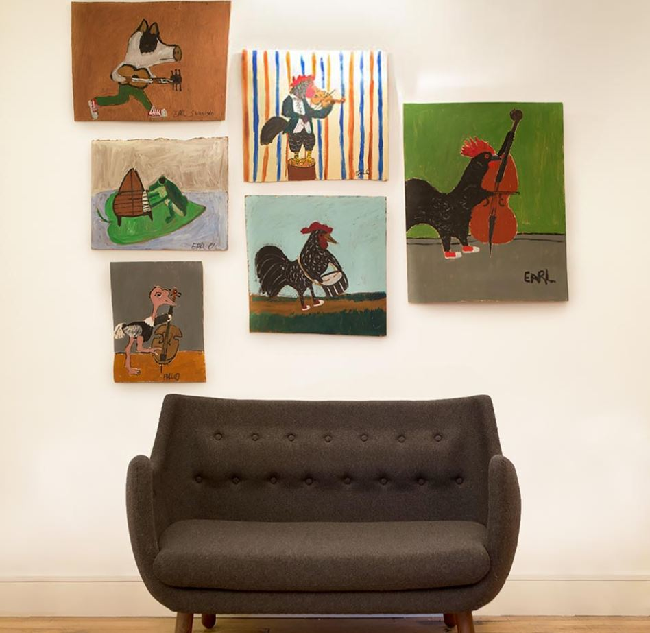 Cozy, black loveseat under paintings of different birds playing instruments in the offices of Heard City. MEP designed by 2LS Consulting Engineering.