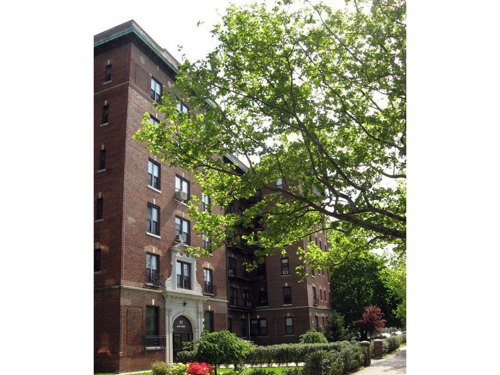 Bushes and trees surrounding a residential building in Brooklyn, New York, on a clear, sunny day. MEP provided by 2LS Consulting Engineering.