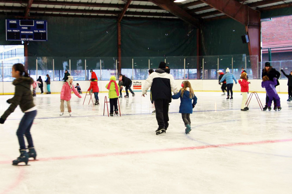 People skating with their children in circles around the Secaucus Ice Skating Rink in New Jersey, with MEP designed by 2L Engineering.