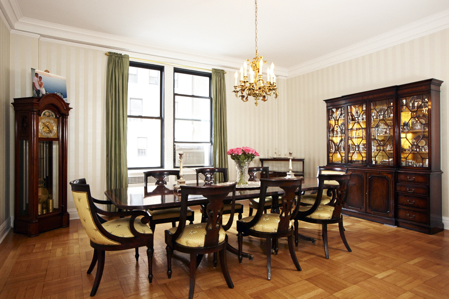 Dining room with antique furniture including a grandfather clock, candle chandelier, and a china cabinet. MEP provided by 2LS Consulting Engineering.