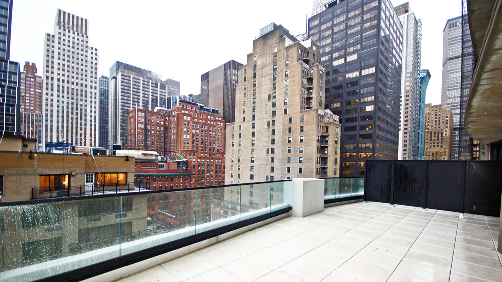 Rainy-day balcony view of New York City from a new mid-rise rental building in Midtown East. MEP designed by 2LS Consulting Engineering.