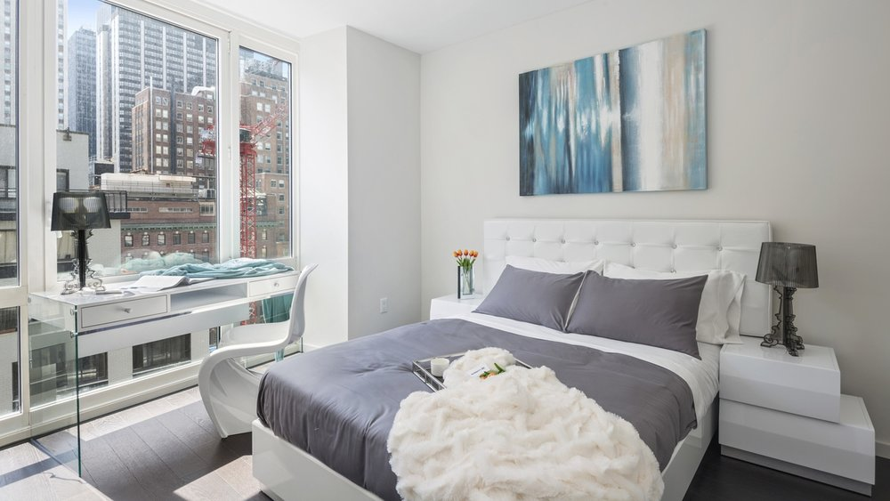Tulips on the bedside table and a fuzzy white blanket on a scandinavian designed bedroom facing views of Manhattan. MEP designed by 2L Engineering.