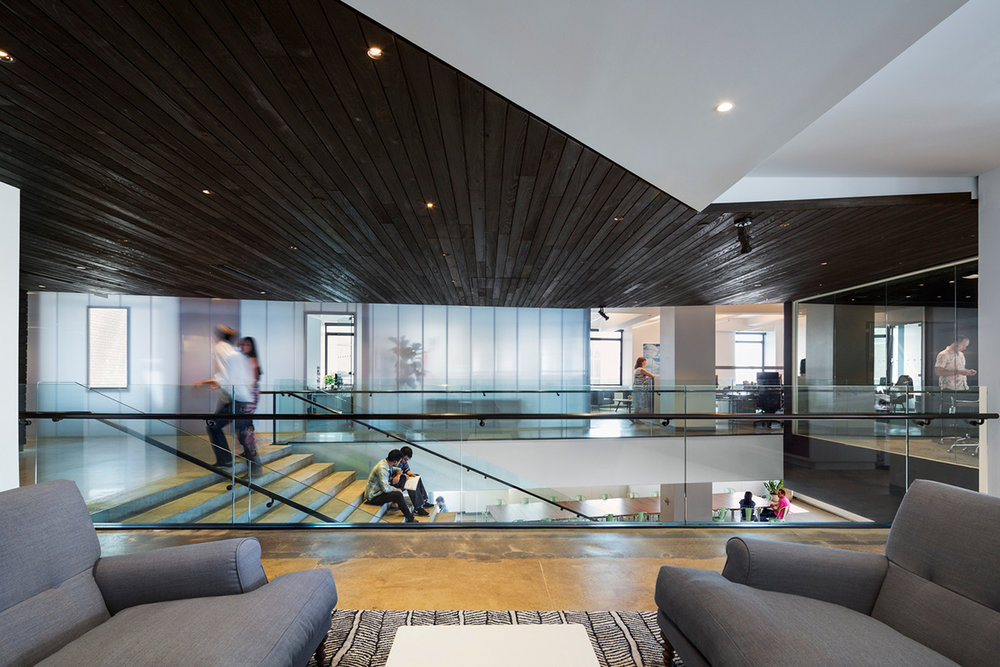 Staircase from the view of a lounge area with people interacting at the offices of Droga5, a New York based global afvertising agency. MEP provided by 2L Engineering