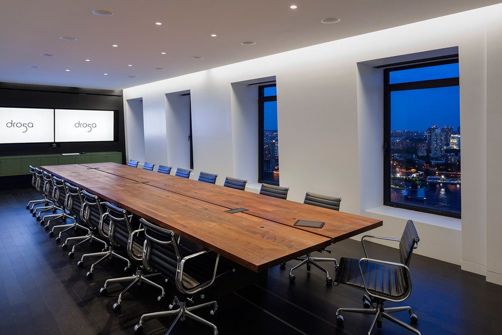 A large conference room with bright TVs showing the Dro5a logo and the New York skyline outside. MEP designed by 2LS Consulting Engineering.