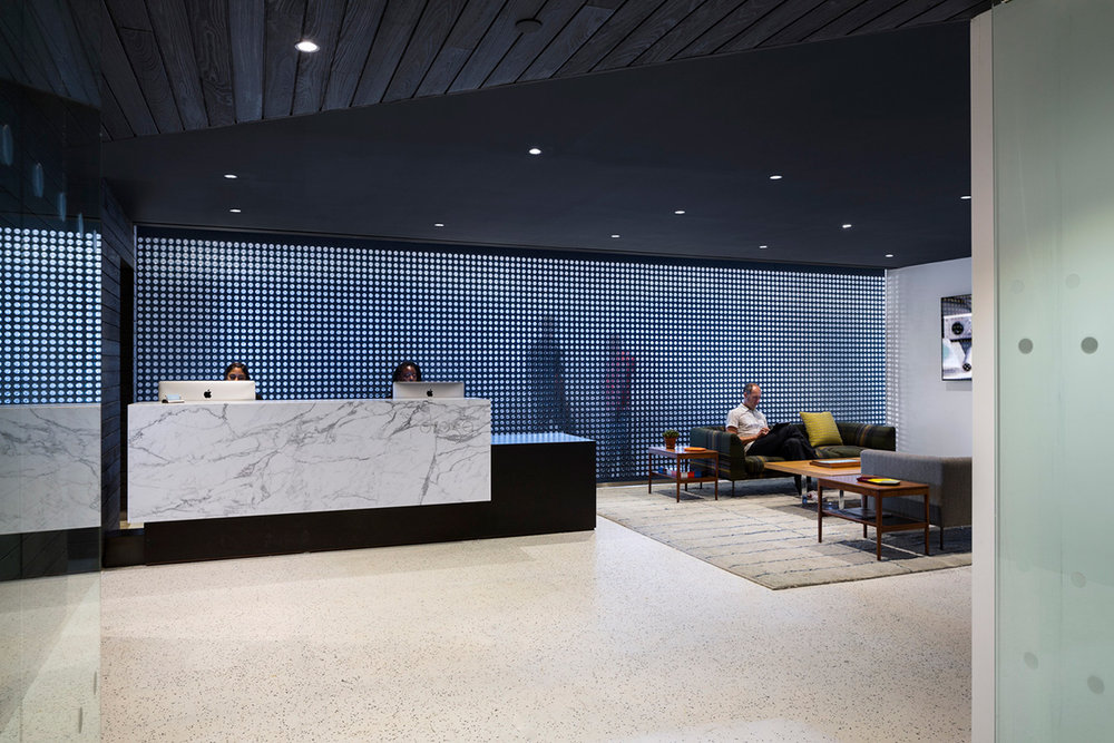 A backlit reception and lounge area with a geometric wall in the offices of Droga 5. MEP provided by 2L Engineering.