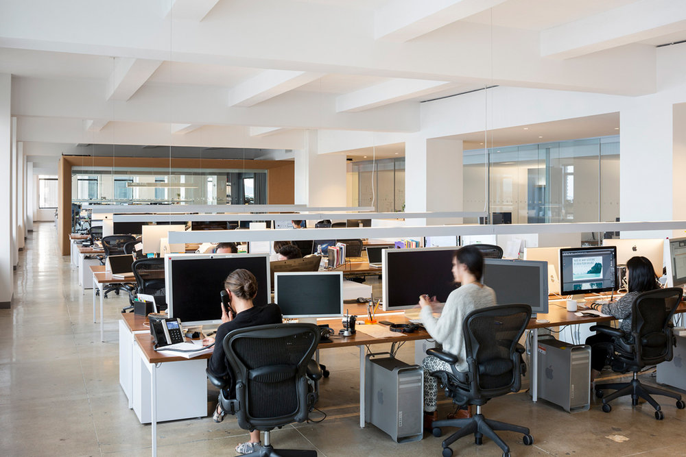 A woman taking a call and two other people working in the Droga5 offices. MEP provided by 2L Engineering.