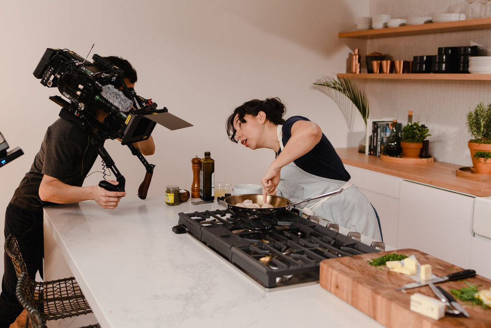 A woman looking into the camera as she points at mushrooms and explains her process in the kitchen studio of Conde Nast in Brooklyn, New York. MEP designed by 2LS.