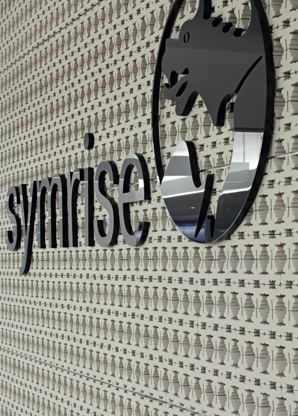 Symrise reception desk with fragrance products on a display shelf and the company logo. MEP designed by 2LS Consulting Engineering.