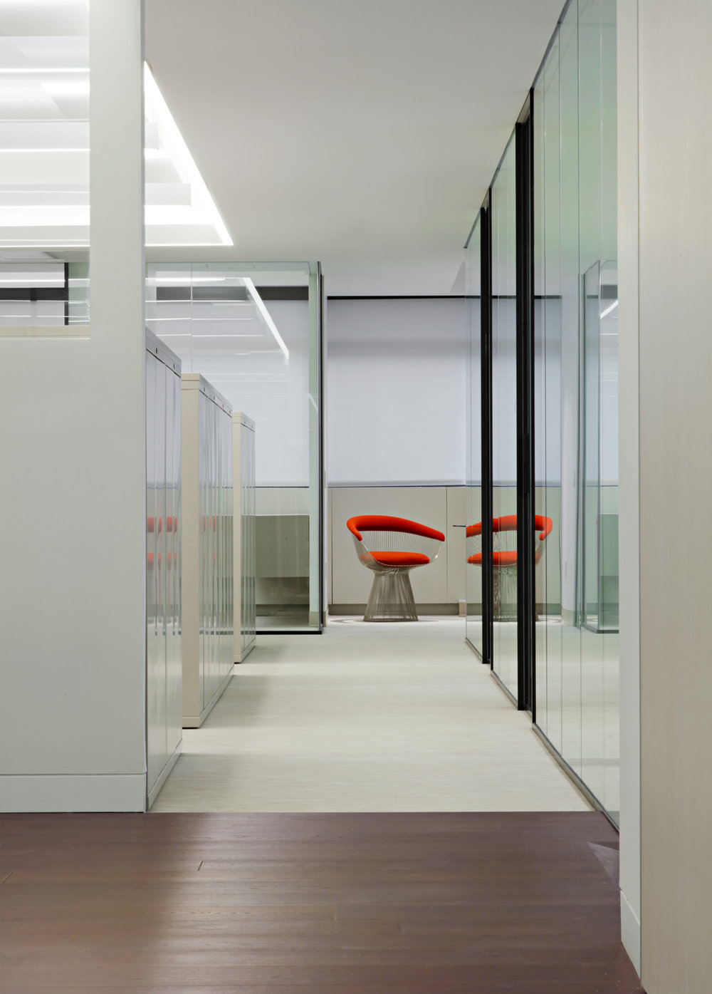 Orange cushioned chair at the end of an office hallway at Symrise, New York. MEP designed by 2LS Consulting Engineering.
