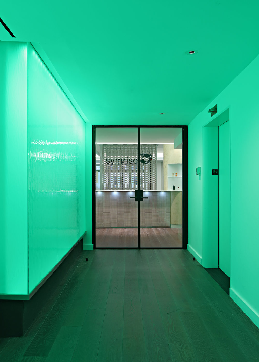 Green lit entrance to the reception area of Symrise offices facing a desk with lighting below the counter. MEP designed by 2LS Consulting Engineering.