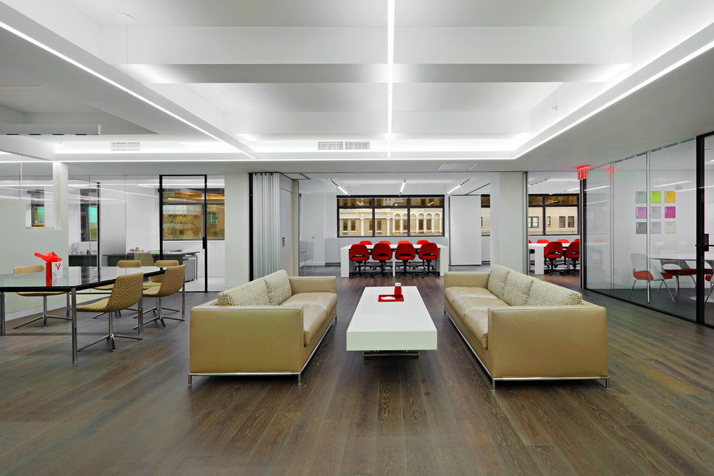 Lounge and break room surrounded by offices and conference rooms with red orange chairs at the Symrise office located in New York. MEP designed by 2L Engineering.