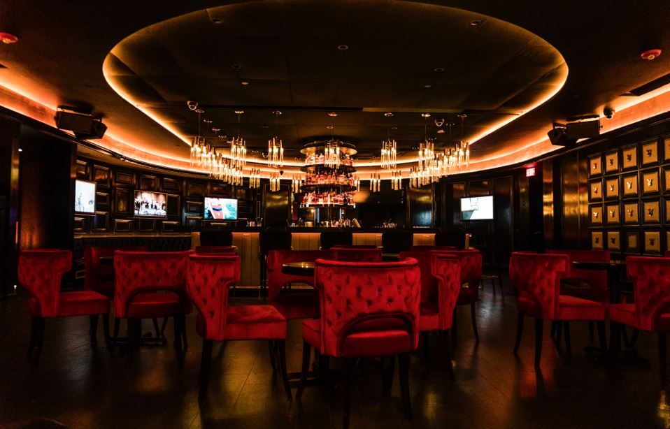 Dimly lit lounge area with red velvet seats, a bar, and tvs at the Playboy Club in New York. MEP Engineering services provided by 2LS Consulting.