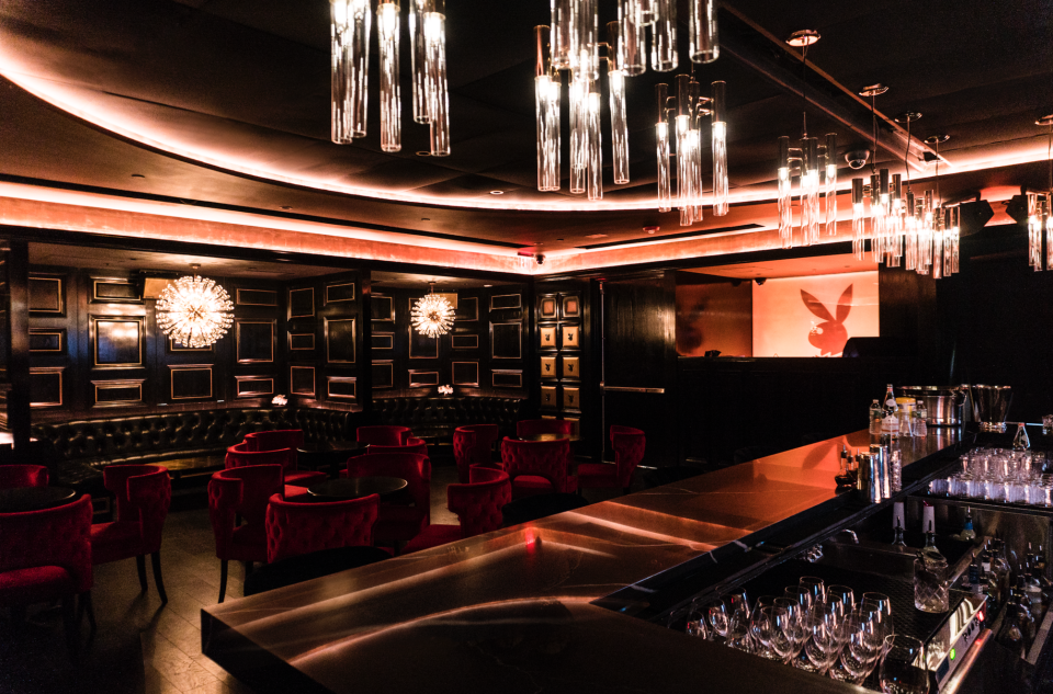 View of the bar and lounge area at the Playboy Club featuring red velvet seats, dandelion chandeliers, and overhead dim lighting. MEP services provided by 2L Engineering.