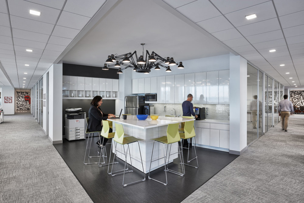 Office kitchenette with a desk lamp chandelier and green bar seats where a woman is working on her laptop as a man makes coffee. MEP provided by 2LS Consulting Engineering.
