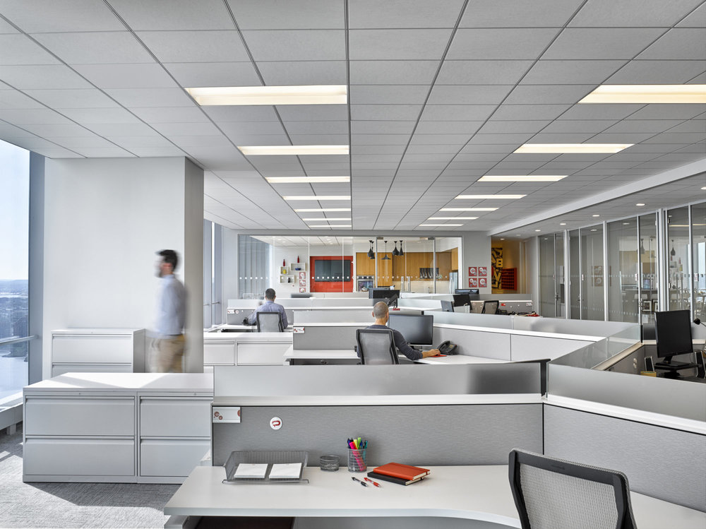 Man looking out the window as people work at their desks in the offices of Padilla CRT in New York. MEP designed by 2LS Consulting Engineering.