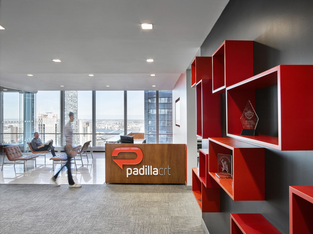 Reception area at Padilla CRT with modern shelving displaying the communication agency's various awards. MEP provided by 2L Engineering.