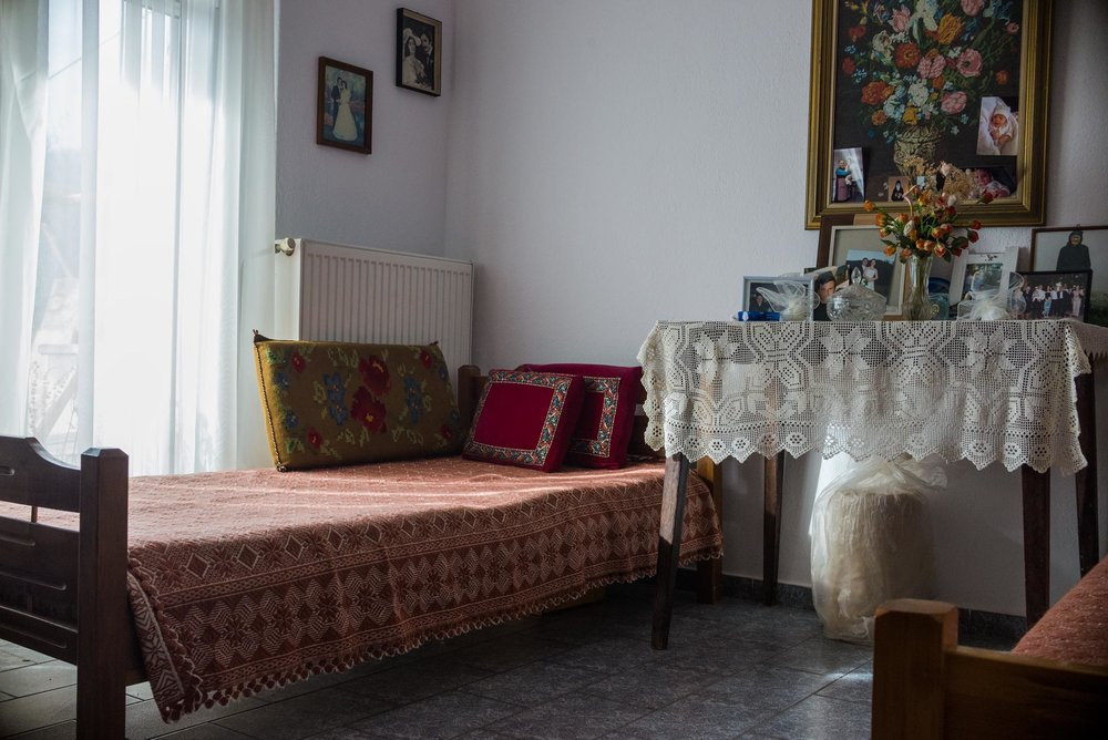 One of the house's rooms filled with family pictures and traditional greek hand-woven textiles.