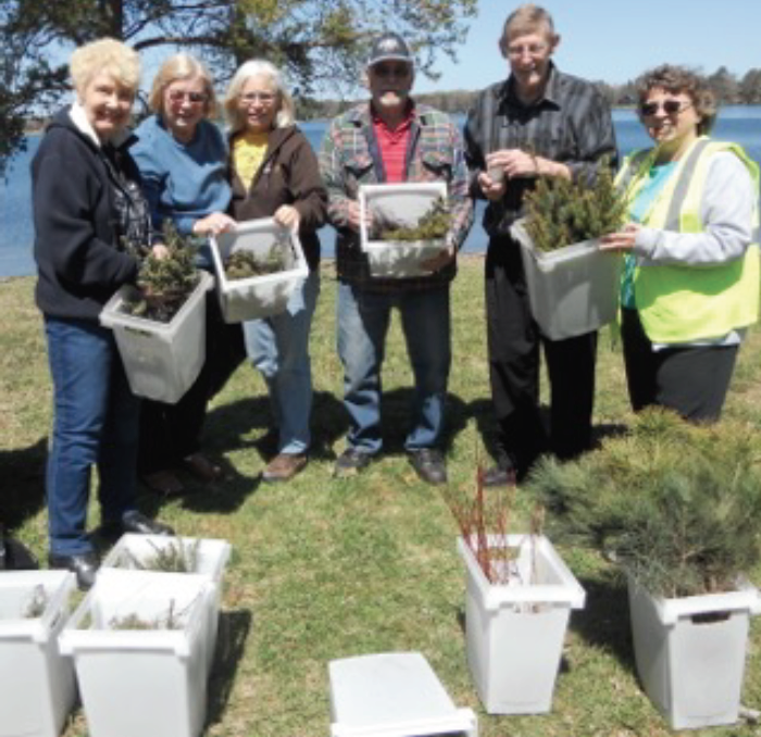 (l to r) Karen Frazier, Edna Baker, Jennifer O'Neill, Jerry Baker, Roy Carlson and Dianne Weisser display the spruce, balsam and dogwood seedlings given away to members on May 7, 2017.