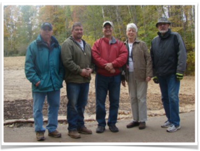 With the new road and pond graded and surfaced, organizers met to check how the newly planted seedlings along the pond edge and hillside were faring. (L to r) Jerry Nelson, Larry Liljenquist, Steve Hughes, Elaine Palthe (who owns the land with the holding pond) and Dave Scott.