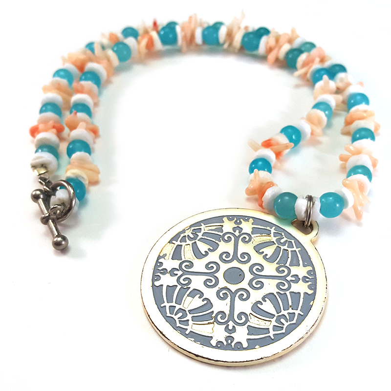 Symmetry   Embrace symmetry with this necklace made from coral and natural stone.