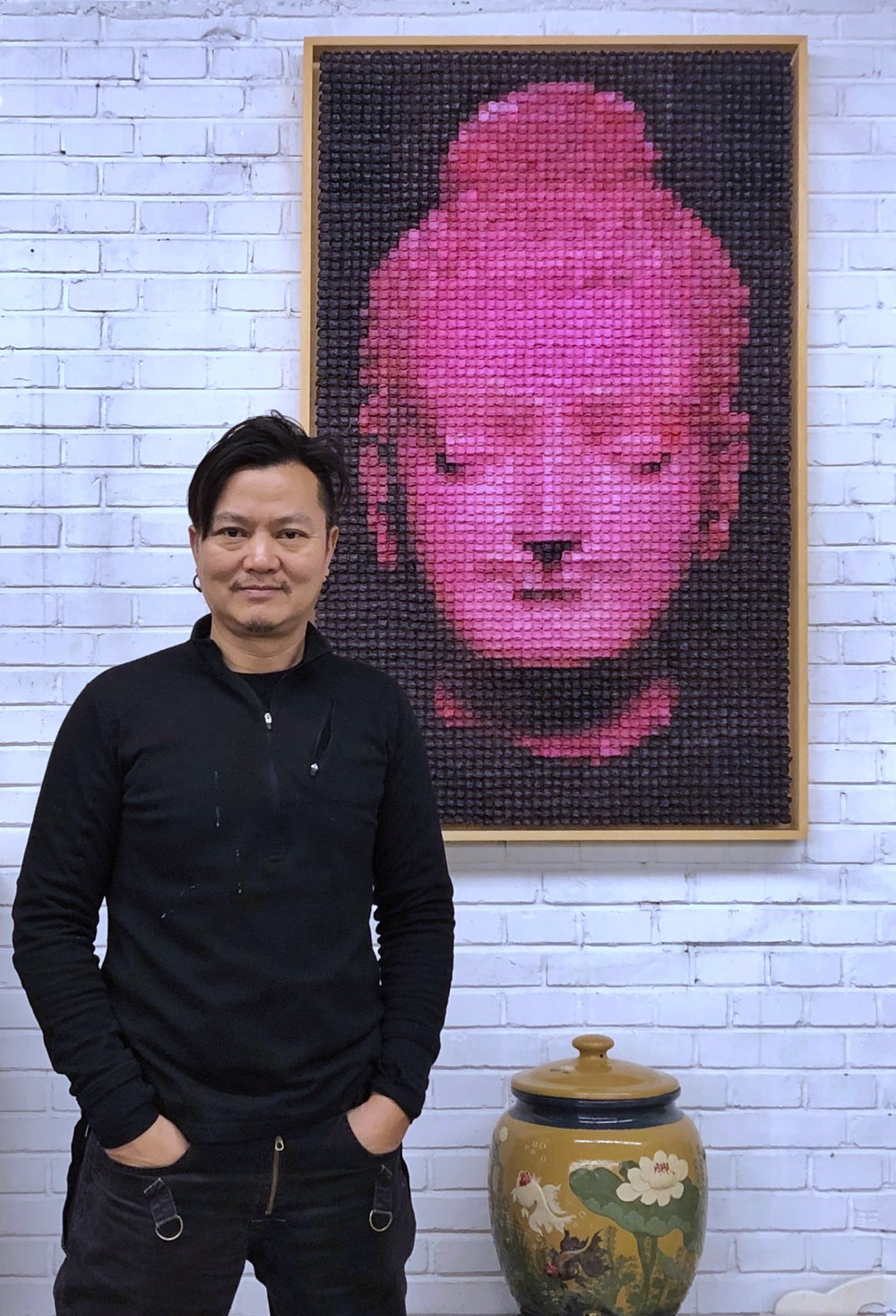 The artist stands in front of the artwork at the collector's house