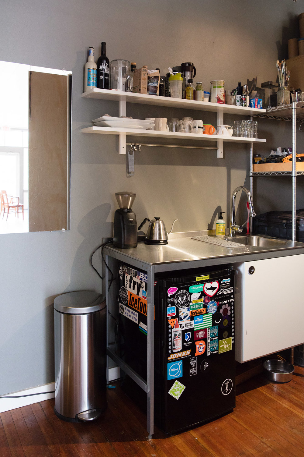 Small kitchenette with sink, coffee goods, and mini fridge.