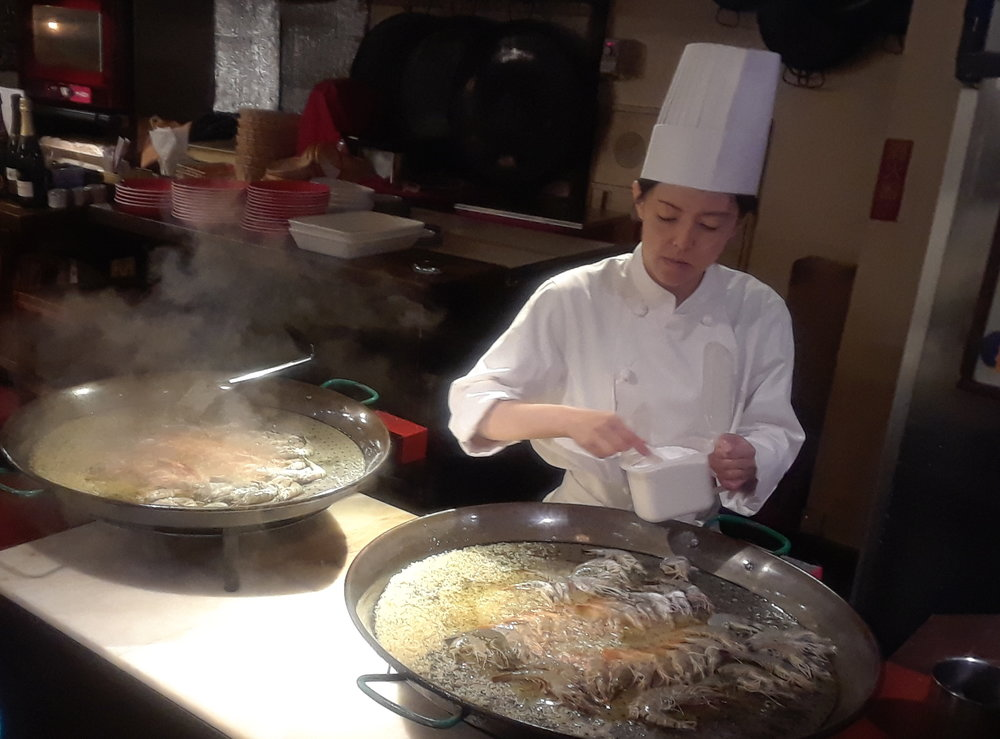 A chef prepares one of the large platters of paella.