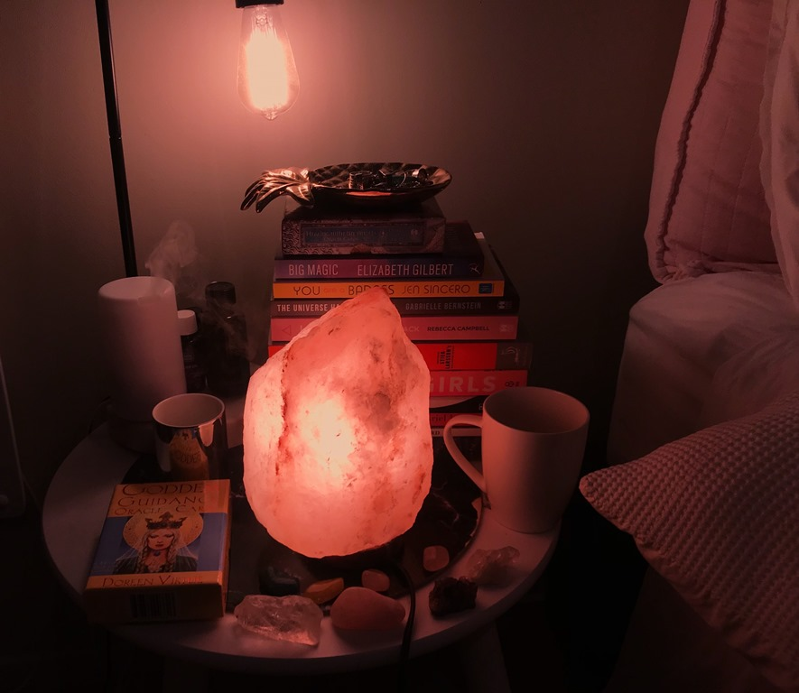 My bedside table with all the holistic goodness. Himalayan salt lamp, oil diffuser, crystals, goddess cards, a stack of books and a cup of herbal tea