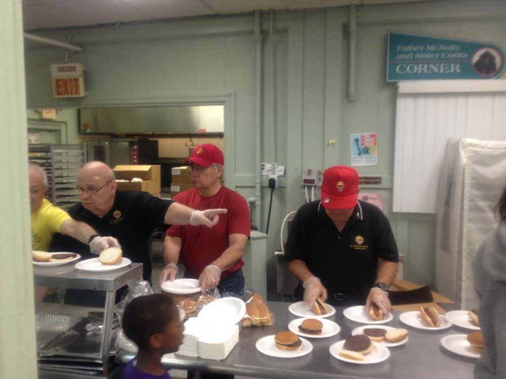 Knights serve lunch to the kids in the basement of St Augustine's