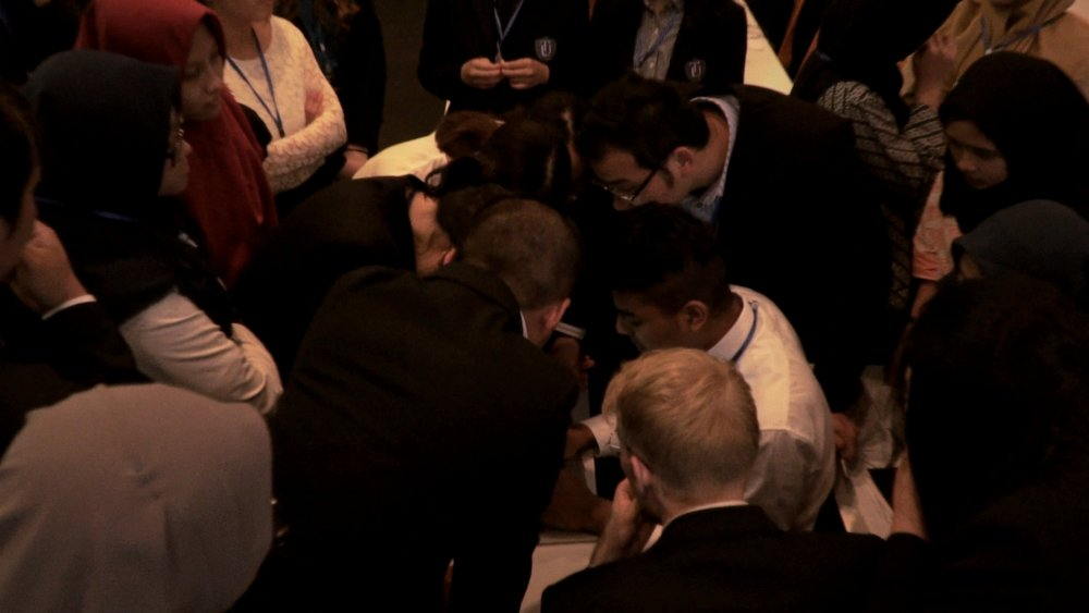 Delegates work against the clock to address a surprised crisis situation planned by TIUMUN team.