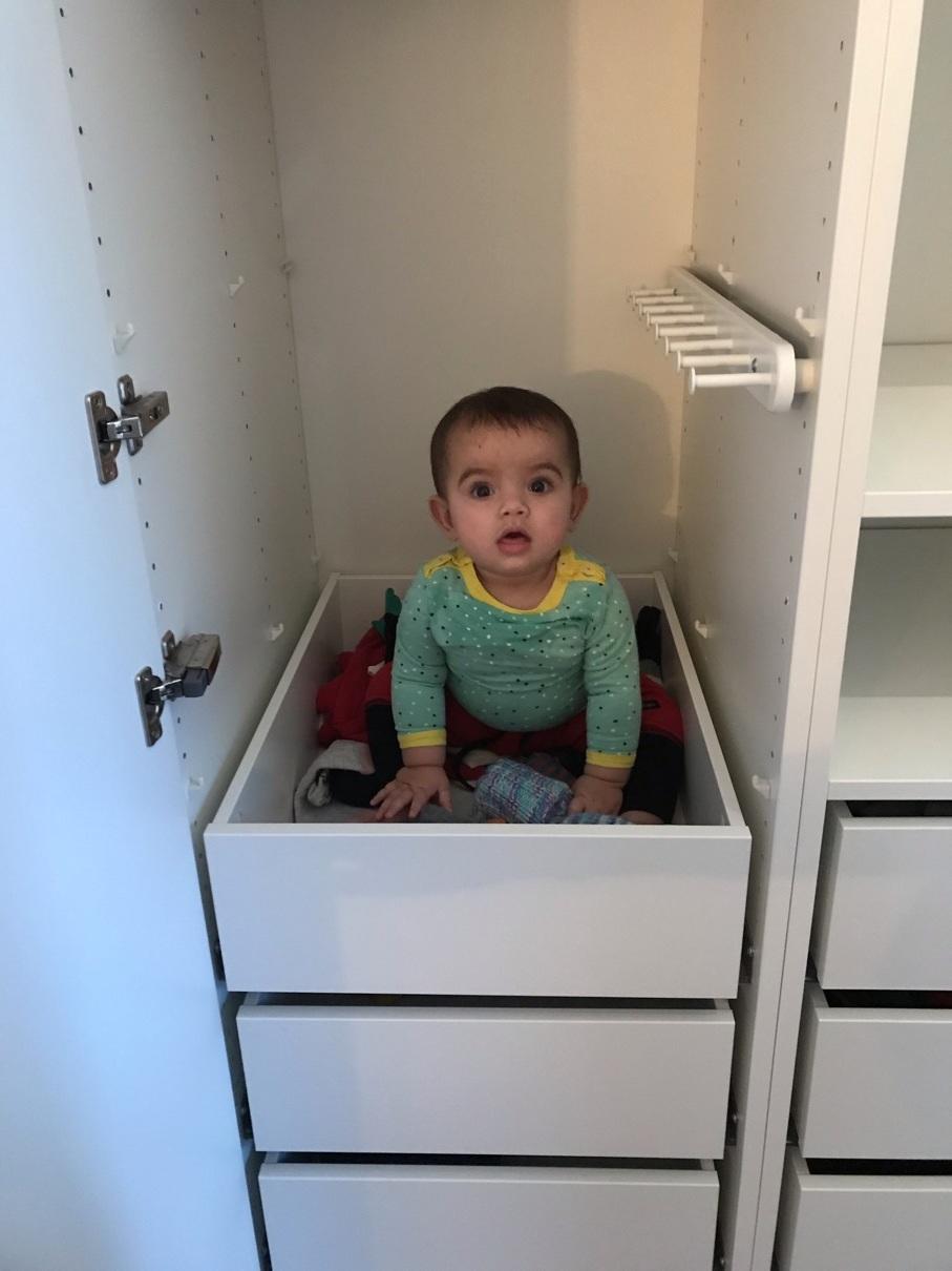 Ella hjälper till genom att sätta sig på sakerna som ska packas, i garderoben…
