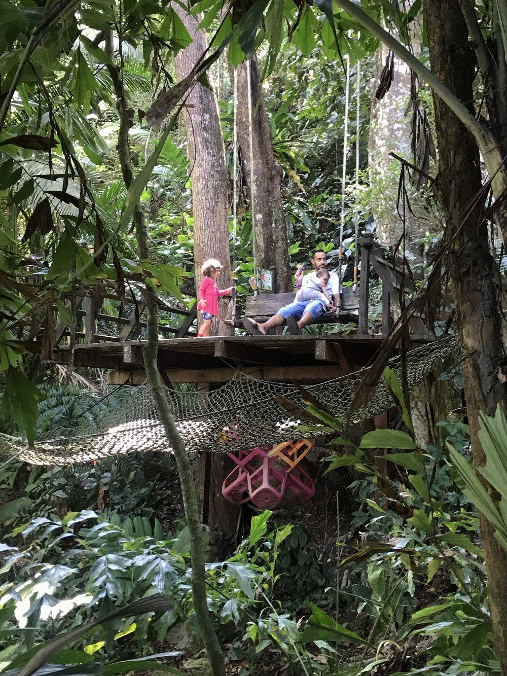 En pappa och två döttrar uppe bland träden.
