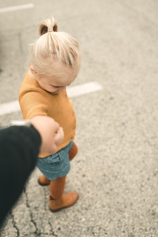 Blond toddler holding her parent's hand